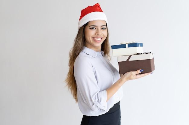 Asistente de oficina de navidad sonriente llevando regalos
