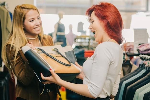 Asistente que da el bolso al cliente