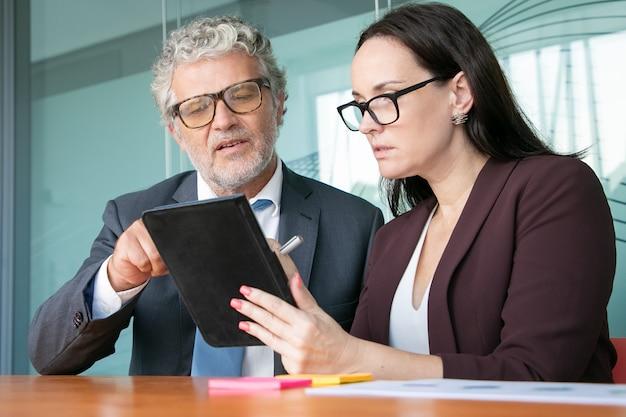 Asistente de sexo femenino que muestra el informe en la tableta al jefe masculino.