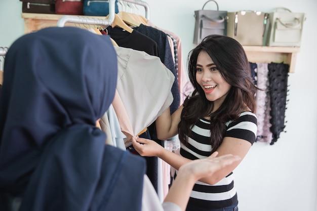 Asistente de tienda femenina ayuda al cliente