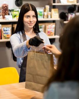 Asistente de ventas de vista frontal repartiendo bolsa de comestibles