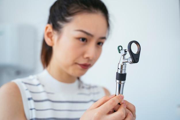 Asistente veterinario chino con una lupa. clínica de salud blanca.