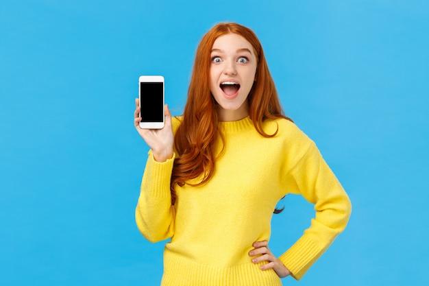 Asombrada e impresionada, emocionada mujer pelirroja con suéter amarillo presenta una nueva aplicación, que muestra la pantalla del teléfono inteligente, sonriendo fascinada con la boca abierta divertida.