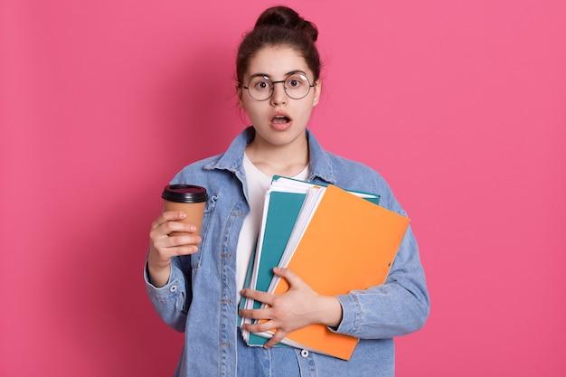 Asombrada joven con boca abierta, sosteniendo café para llevar y carpeta de papel