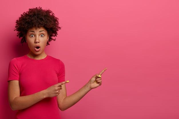 Asombrada mujer afroamericana señala lejos, muestra un espacio en blanco para su anuncio, aturdida por una oferta increíble, abre la boca, vestida de manera informal, aislada sobre una pared rosa. dios mío, mira esto