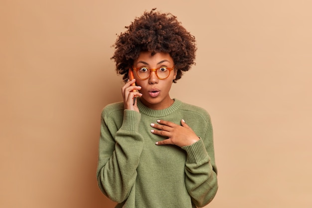 Asombrada mujer de pelo rizado que habla por teléfono se entera de que ocurrió un evento terrible sostiene un teléfono inteligente cerca de los soportes para las orejas con la respiración contenida usa lentes transparentes y un suéter aislado sobre una pared beige