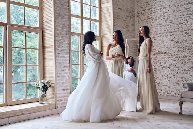 Asombrado por la belleza de las novias. dos atractivas mujeres jóvenes sonriendo mientras mira a la novia en el probador