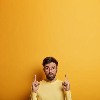Asombrado estudiante masculino barbudo señala arriba con el dedo índice, demuestra un nuevo producto, habla de ventas, jadea de miedo, posa sobre una pared amarilla, espacio en blanco para su contenido promocional.