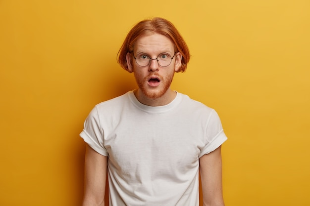 Asombrado modelo masculino de pelo rojo abre la boca con sorpresa