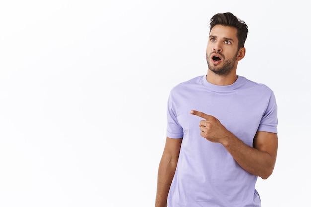 Asombrado y sin palabras sorprendido chico guapo hipster con camiseta morada, con la mandíbula caída y jadeando asombrado, apuntando mirando a la izquierda con asombro y deambulando, ver algo increíble, promoción excepcional