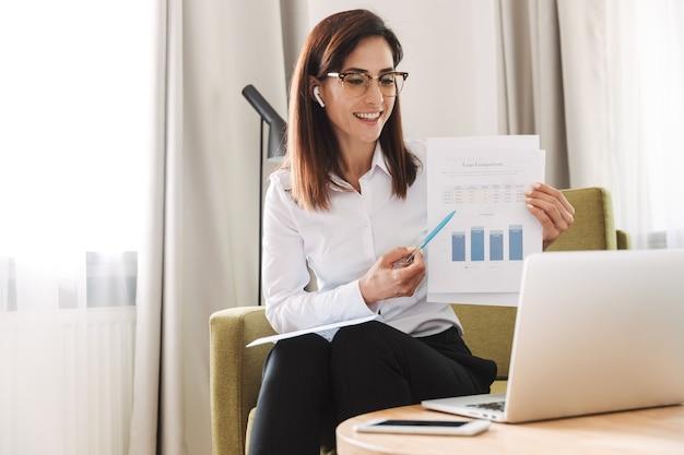 Asombrosa mujer de negocios joven hermosa concentrada en ropa formal en el interior en casa hablando usando una computadora portátil con auriculares mostrando gráficos.