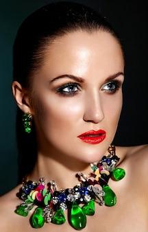 Aspecto de alta moda. retrato de primer plano de glamour de hermosa morena caucásica joven modelo con cabello sano con piel limpia perfecta y joyas accesorios azules