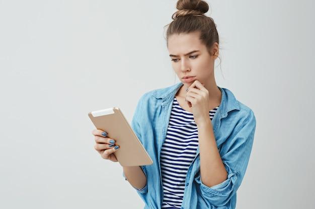 De aspecto serio, atractiva y moderna mujer moderna que controla la tabla de trabajo remoto desde casa con tableta digital mirando la pantalla de visualización reflexiva, tocando el labio pensando, de pie