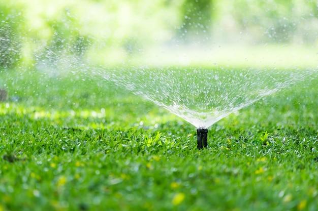 Aspersor automático de césped para jardín en acción regando pasto