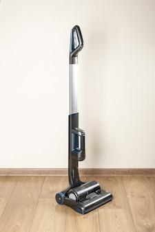 Aspirador de mano con depósito de polvo pequeño en una habitación vacía. aspiradoras verticales inalámbricas sin bolsa de polvo con filtro ciclónico