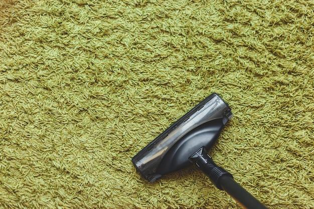 Aspiradora de cepillo en la alfombra verde, vista desde arriba.