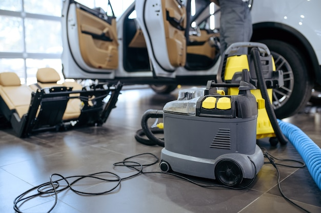 Aspiradora, limpieza en seco y concepto de servicio de detalle. lavado de vehículos químicos en el garaje, cuidado minucioso del automóvil.