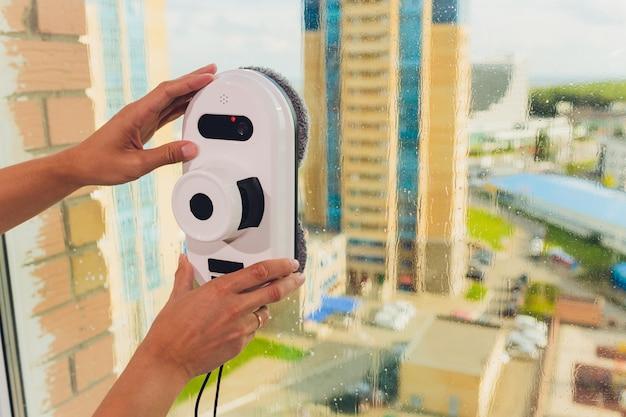 Aspiradora robot limpieza ventana en alto edificio al aire libre.