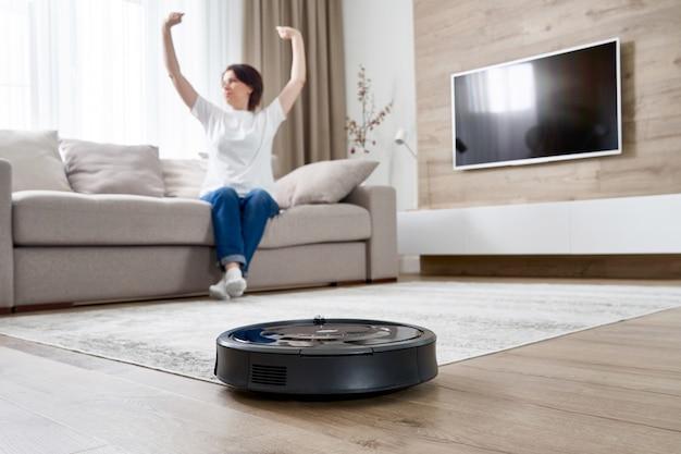Aspiradora robótica limpiando la habitación mientras la mujer descansa sobre el sofá