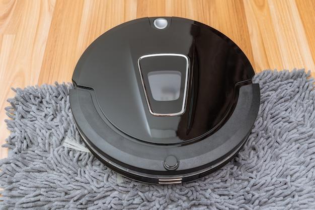 Aspiradora robótica sobre piso de madera laminada tecnología de limpieza inteligente en el hogar