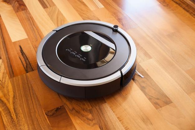 Aspiradora robótica sobre piso de madera laminada tecnología de limpieza inteligente