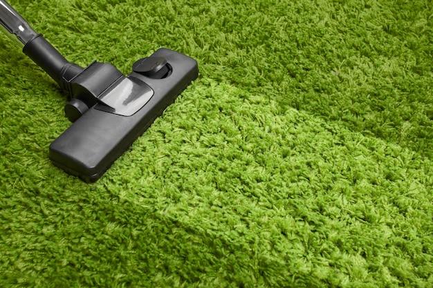 Aspiradora sobre alfombra verde