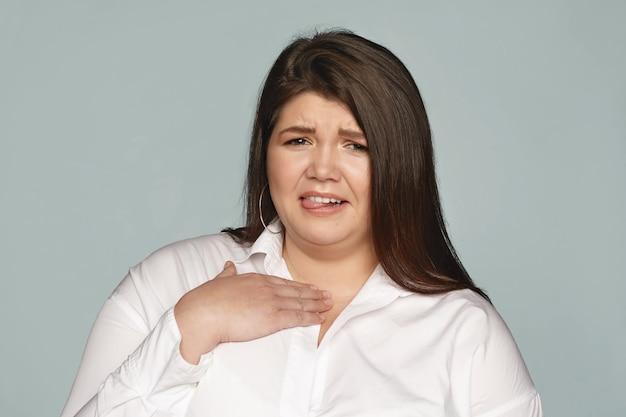 Asqueroso, ew. retrato de mujer europea gordita joven emocional disgustada haciendo muecas, sacando la lengua y sosteniendo la mano sobre su pecho, sintiéndose enferma debido al olor desagradable. mal olor y asco