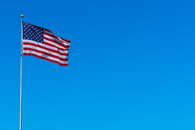 Asta de bandera del estado unido de américa en fondo del cielo azul