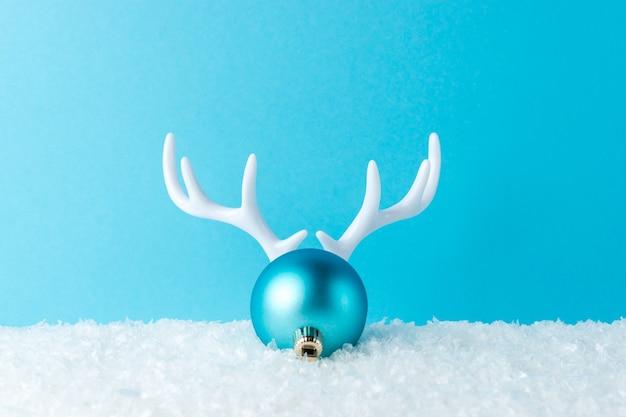 Astas de reno blanco con nieve y adornos navideños