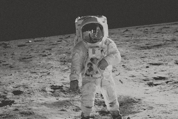 Astronauta caminando sobre la luna en tono blanco y negro.