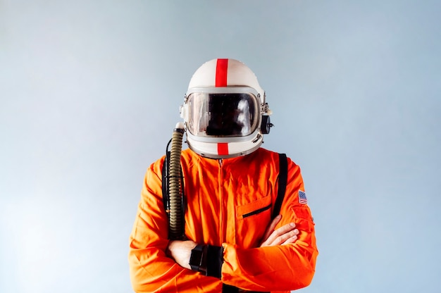 Astronauta con casco cosmonauta vistiendo traje espacial naranja con casco blanco