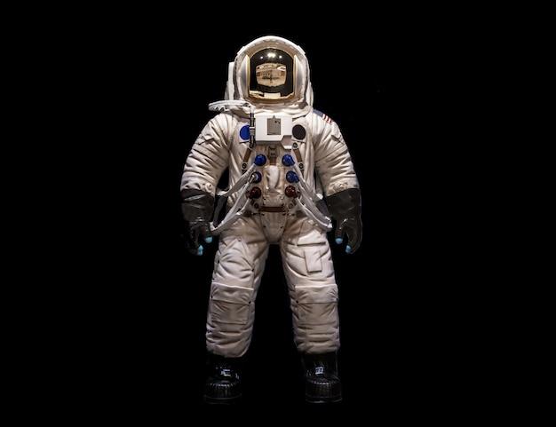 Astronautas en trajes espaciales sobre un fondo negro.