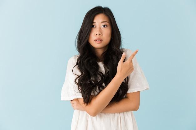 Asustada joven bella mujer asiática posando aislada sobre pared azul apuntando