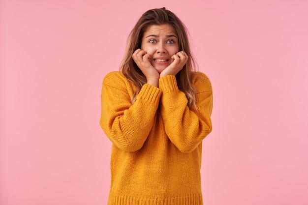 Asustada joven mujer de cabello castaño con maquillaje natural tomados de la mano en las mejillas mientras posa en rosa, cejas fruncidas y mostrando sus dientes mientras