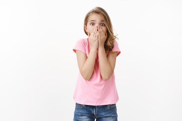 Asustada y preocupada joven linda niña rubia pidiendo ayuda, entrando en pánico, sintiéndose asustada jadeando sorprendida cubra la boca con las palmas, asustada cámara molesta y sin palabras, preocupación porque un amigo se metió en problemas