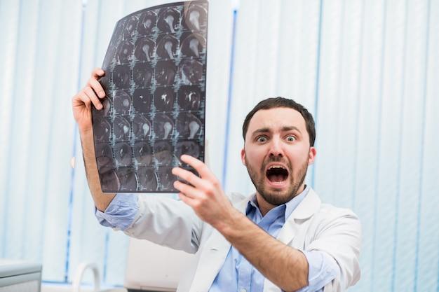 Asustado preocupado médico revisando la exploración de rayos x mirando a la cámara en el interior de la oficina