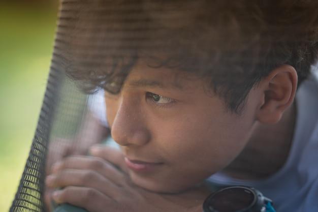Asustado y solo, un niño asiático joven que está en alto riesgo de ser intimidado