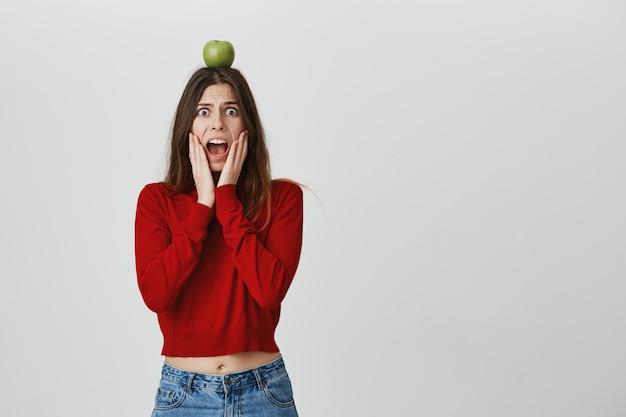 Asustando a la niña preocupada que sostiene la manzana en la cabeza como un objetivo de arquero