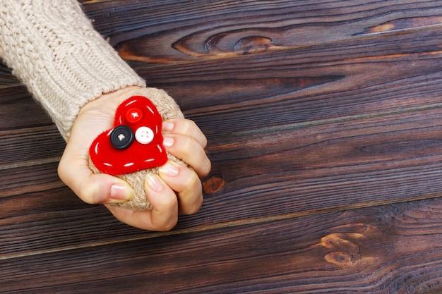 Ataque al corazón con ambas manos sobre fondo de madera