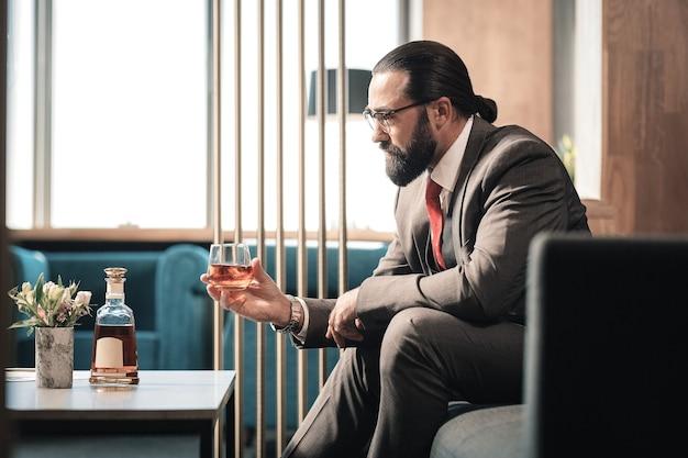 Ataque de nervios. hombre de negocios maduro barbudo que sufre de crisis nerviosa bebiendo alcohol
