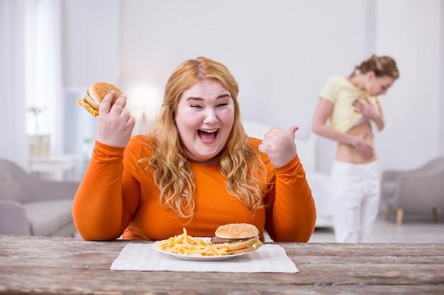 Ataque de nervios. mujer gorda preocupada comiendo una ensalada y apuntando a su amiga delgada