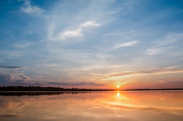 Atardecer en el lago. hermosa puesta de sol detrás de las nubes sobre el fondo del paisaje del lago sobre.