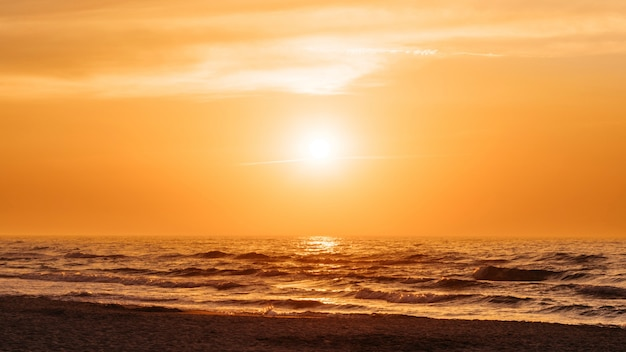 Atardecer naranja en una playa en verano