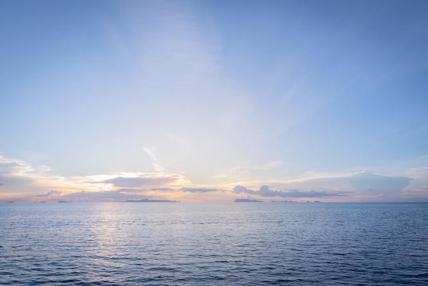 Atardecer de playa de verano con mar azul y cielo dorado