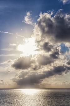 Atardecer sobre el mar con los rayos del sol entre las nubes.
