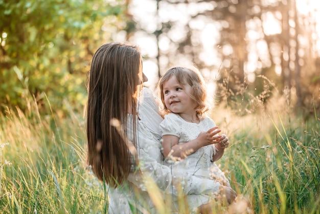 Atardecer de verano en el parque o bosque. hija en un caballito con su madre.