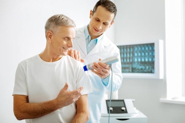 Atención médica. agradable terapeuta profesional positivo de pie detrás de su paciente y utilizando un dispositivo de ultrasonido especial para controlar la salud de sus pacientes