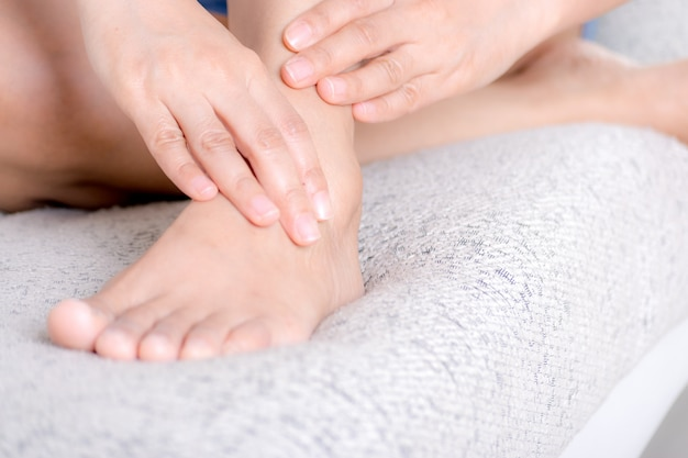 Atención médica y concepto médico. mujer joven del primer que se sienta en el sofá y que siente dolor del tobillo y que ella da masajes a su tobillo en casa.