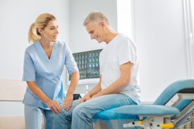 Atención médica. encantado de agradable doctora mirando a su paciente y haciendo fisioterapia mientras trabajaba en el hospital