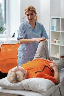 Atención médica. enfermero profesional mirando a su paciente mientras masajea su pierna